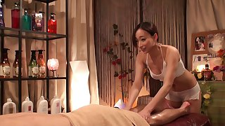 Fit and scantily clad Asian masseuse climbs on him